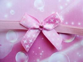 Voor de allerkleinste super smal roze haarbandje met strikje.