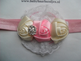 Smalle roze baby haarband met kant en roosjes.