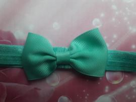 Smalle groene baby haarband met klein strikje (7cm)..