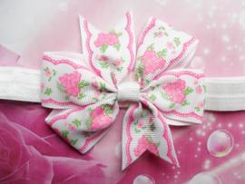 Smalle witte baby haarband met bloemen strik.