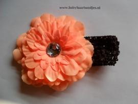 Gehaakte donker bruine haarband met oranje bloem.