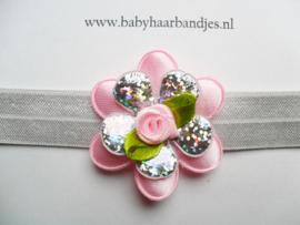 Smalle grijze baby haarband met roze/zilveren bloem.