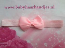 Smalle roze baby haarband met strikje.