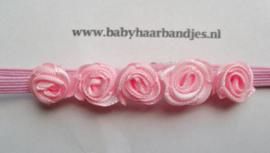 Voor de allerkleinste super smal roze haarbandje met roze roosjes.