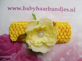 Gehaakte gele haarband met grote bloem.