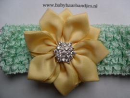 Gehaakte mint groene haarband met gele bloem.