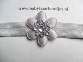 Smalle grijze baby haarband met bloemetje.