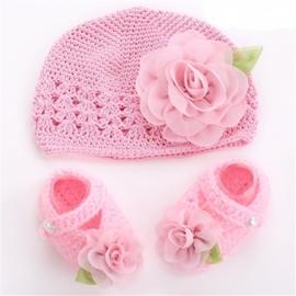 Gehaakt roze baby mutsje met bloem en slofjes.