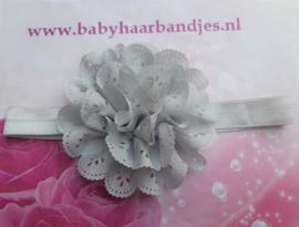 Smalle grijze  baby haarband met kanten bloem.
