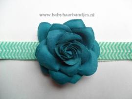 Smalle bewerkte groene babyhaarband met roosje.