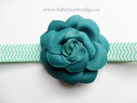 Smalle groene baby haarband met roosje.