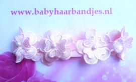 Smalle roze baby haarband met 5 kanten bloemen.