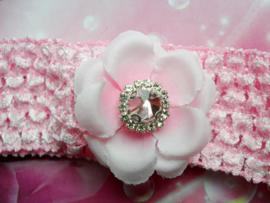 Gehaakte roze haarband met bloemetje.