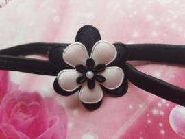 Smalle zwarte baby haarband met zwart/witte bloem.