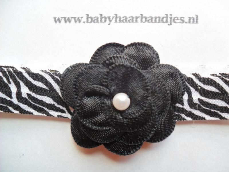 Smalle wit/zwarte baby haarband met zwart bloemetje.
