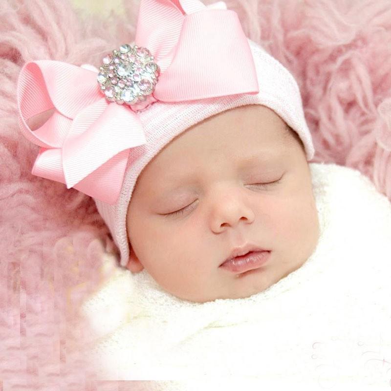 New born wit/roze gestreept baby mutsje met grote roze strik en steen.