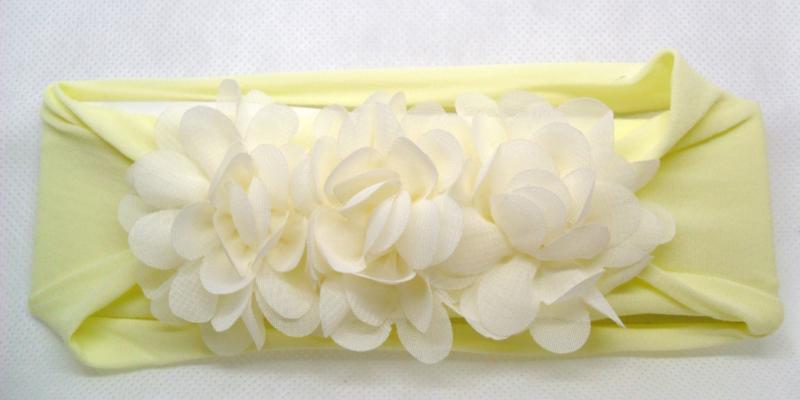 Brede zacht gele nylon baby haarband met 3 ecru chiffon toefjes.