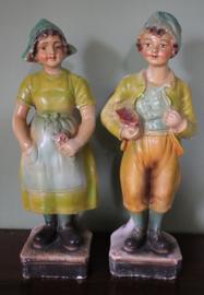 Twee gipsen beelden van een jongen en een meisje