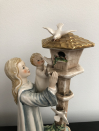 Porseleinen beeld Goebel: Moeder en kind bij duiventil. Ontworpen door Charlot Byi met nummer 37.