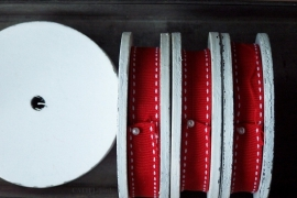 Band - rood met wit stiksel op wit houten spoel