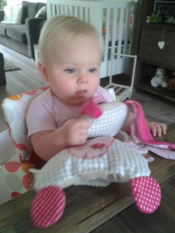 Kleine meid blij met haar knuffelkonijn roze, zand met bloemen