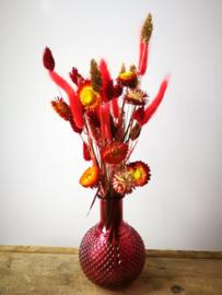 Vaas in warm rood met boeket droogbloemen