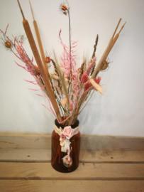 Bruine glazen vaas met roze droogbloemen
