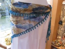 D26A Driehoeksjaal melée stof met met turquoise, blauwe en bruine motieven en een turquoise kralenrand.
