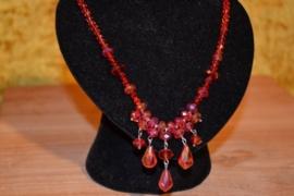 Halsketting, rode kristalfacetkralen, pegels aan de ketting