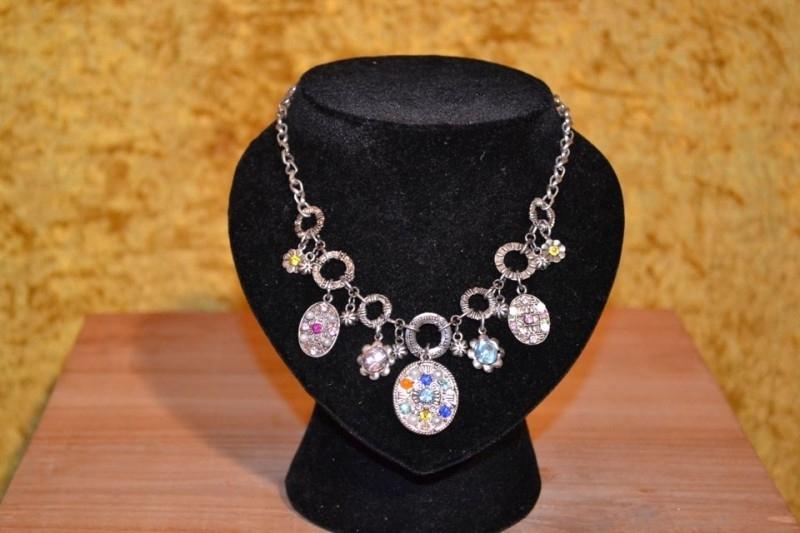 Halsketting, ronde zilverkleurige ornamenten versierd met gekleurde strassstenen