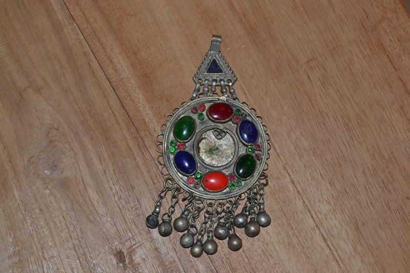 Tribal ornament - driehoek met rond. Gekleurde stenen, kettingfranjes met belletjes
