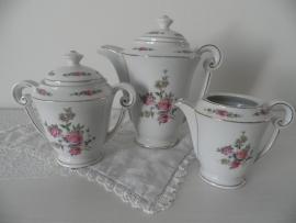 Porseleinen theepot, suikerpot en melkkannetje met bloemmotief