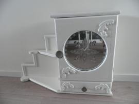 Wit houten kastje met deurtje en bewerkte spiegel, laadje en plankjes ernaast VERKOCHT