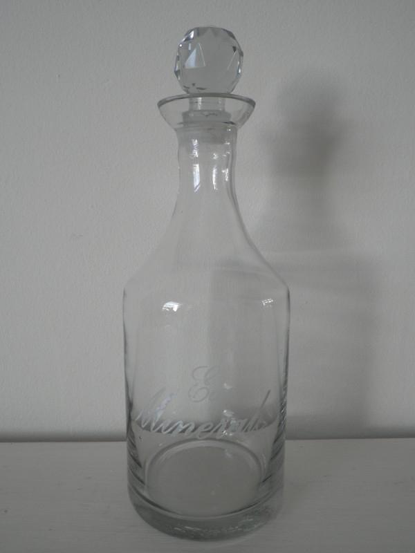 Glazen fles met dop en tekst ``eau minerale``
