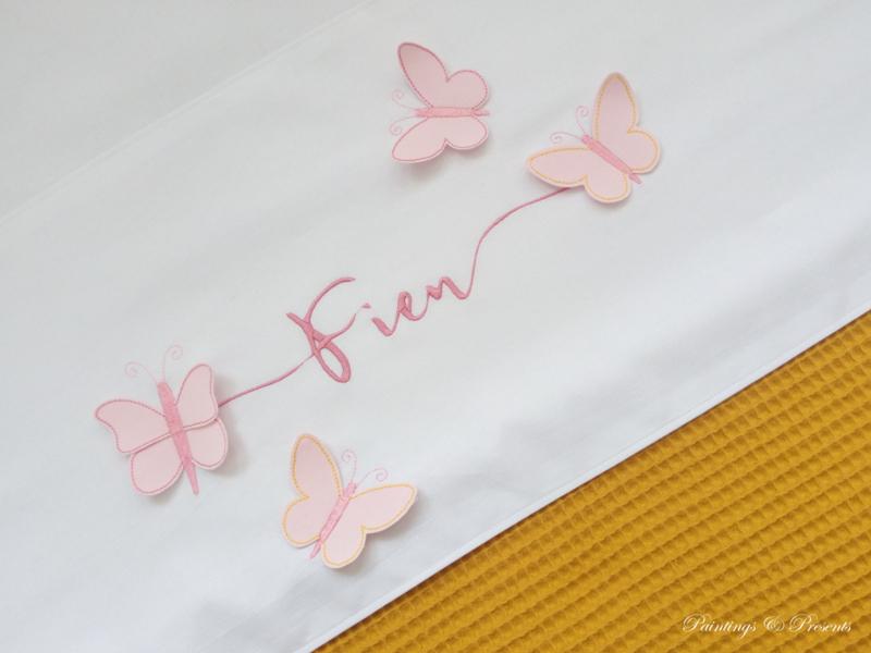 Wit lakentje met naam en 3D vlinders roze/oker en oud roze borduring