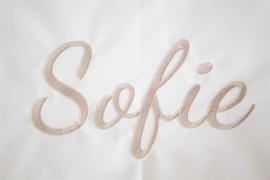 Wit ledikantlaken met sierlijk geborduurde naam ** zand**