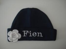 donkerblauw mutsje met naam en wit gehaakte bloem