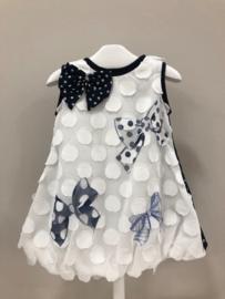 Elsy, wit jurkje met donkerblauwe strikken