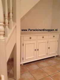 Kast met porseleinen kastnoppen onder de trap