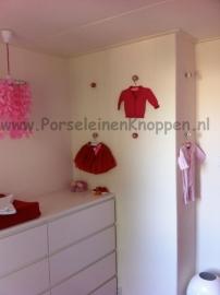 Babykamer met kastknoppen in de muur als kapstokken