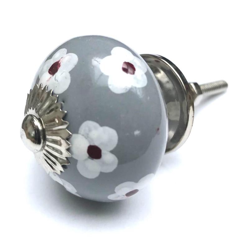 grijze kastknop met witte bloemen