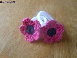 Zachte elastiekjes, groot, wit met fuchsia roze gehaakt bloemetje met donkerblauw hartje.