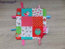 Labeldoekje, patchwork met vogeltjes/hertjes en rood badstof en 8 labeltjes.