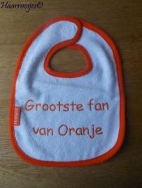 """Slabbetje, wit badstof met oranje biaisband """"Grootste fan van Oranje""""."""
