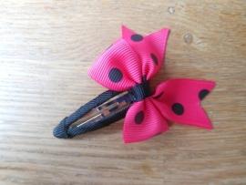 Haarspeldje meisje, met een fuchsia roze met zwarte strik.