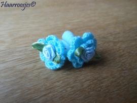 Zachte elastiekjes, klein, lichtblauw met lichtblauw gehaakte bloemetjes en lichtblauwe roosjes.