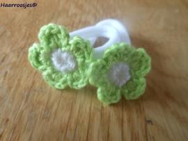 Zachte elastiekjes, groot, wit met groen gehaakte bloemetjes met wit hartje.