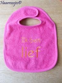 "Slabbetje, fuchsia roze badstof met fuchsia roze  biaisband ""Ik ben lief""."