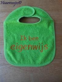 """Slabbetje, groen badstof met groen biaisband """"ik ben eigenwijs""""."""