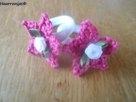 Zachte elastiekjes, groot, wit met fuchsia roze sterretjes en wit roosjes.
